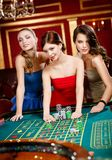 Three women bet playing roulette Stock Image