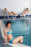 Three women in bikini in swimming pool Stock Image