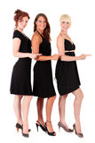Three women black dresses. Three attractive young women in black dresses with pointing hands. Studio shot. White background stock images