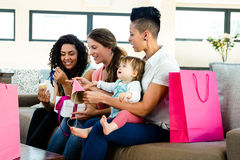 Three women celebrating a babies first birthday. Three women sitting on a couch celebrating a babies first birthday royalty free stock photos