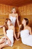 Three women chatting in sauna Stock Image