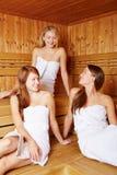 Three women chatting in sauna Stock Image