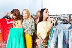 Three women choose clothes in the mall Royalty Free Stock Images