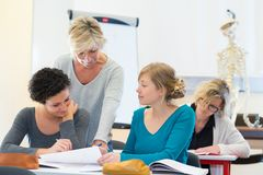 Three women in classroom with teacher royalty free stock photography