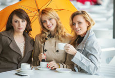 Three women, the coffee and the umbrella Stock Photo