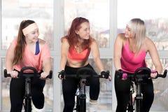 Three women cycling in class Stock Photos