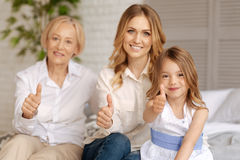 Three women of different age showing thumbs up stock photo