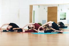 Three young women doing Pilates exercising in the yoga class stock image