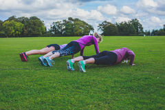 Three women doing push ups in park Stock Photography