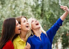 Three women doing a selfie in the park Royalty Free Stock Photo