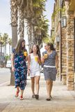 Three women drinking fruit smoothies while walking down street stock photo