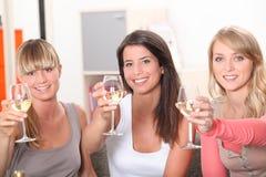 Three women drinking wine Stock Images