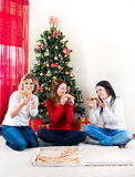 Three women eating pizza in front of Christmas tree Royalty Free Stock Photo