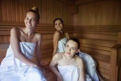 Three women enjoying a hot sauna Stock Image