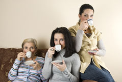 Three women friends drinking coffee. Three women friends enjoying a coffee and a conversation in living room,sitting all on sofa,see more in People on couch Royalty Free Stock Photography