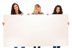 Three women friends holding a blank billboard and smile Stock Photo