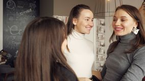 Three women friends are hugging together greeting. Friendly meeting in cafe. Friendship concept stock footage