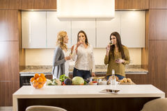 Three women friends toasting white wine in modern kitchen Royalty Free Stock Images