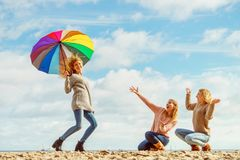 Women holding umbrella having fun with friends Stock Images