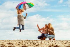 Women jumping with umbrella stock photos
