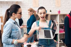Three women at garment factory. They are looking for desing for new dress on laptop. stock photos
