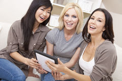 Three Women or Girl Friends Using Tablet Computer. Three beautiful young women or girl friends at home using tablet computer and laughing Royalty Free Stock Photos