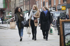 Three women go with bags down the street, discussing Stock Photos