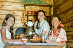 Three women having tea. In russian traditional interior Royalty Free Stock Photography