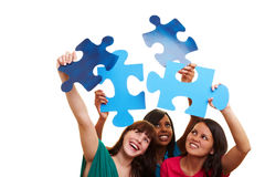 Three women holding big jigsaw Stock Photos