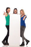 Three  women holding a  billboard and make the ok sign Royalty Free Stock Photos
