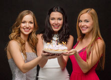 Three women holding cake with candles Royalty Free Stock Photos