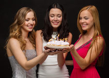 Three women holding cake with candles Stock Photos