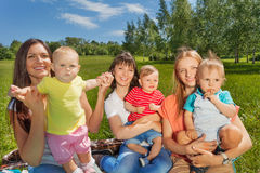 Three women holding cute babies sitting together stock photography