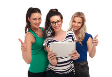 Three women holding a tablet  make the ok sign Stock Image