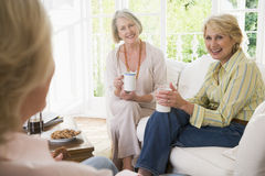 Three Women In Living Room With Coffee Smiling Royalty Free Stock Photography