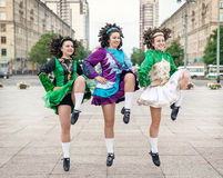 Three women in irish dance dresses dancing Stock Photography