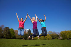Three women jumping into the air Stock Images