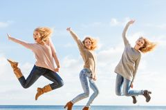 Three women jumping. Three women full of joy jumping around with sky in background. Female friends having fun outdoor Stock Images