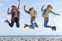 Three women jumping stock photos