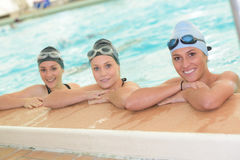 Three women leaning on side pool Stock Photos