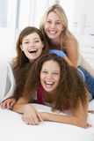 Three women in living room playing and smiling Stock Image