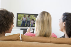 Three women in living room watching television Stock Images