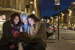 Three women looking at a digital tablet in the city Royalty Free Stock Images