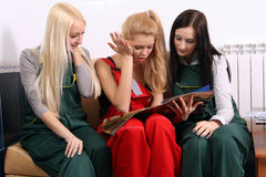 Three women looking magazine Royalty Free Stock Images