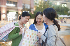 Three Women Looking Into Shopping Bag Royalty Free Stock Photos