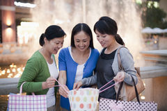 Three Women Looking Into Shopping Bag Royalty Free Stock Photo