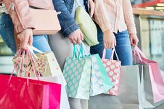 Three women with many shopping bags. As a symbol of consumption and purchasing power Stock Image