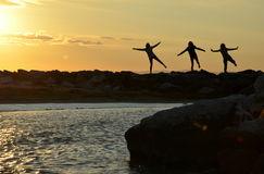 Three women by morning excercises at sea by sunrise Royalty Free Stock Photo