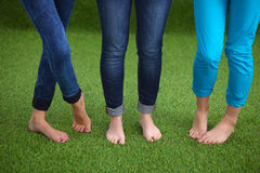 Three women with naked feet standing in grass Royalty Free Stock Photo