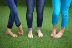 Three women with naked feet standing in grass Stock Photos